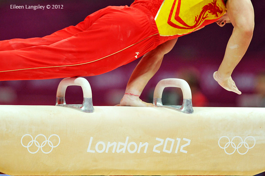 A geeneric image of a Chinese gymnast competing on Pommel Horse decorated with the Olympic Rings and Logo at the 2012 London Olympic Games.