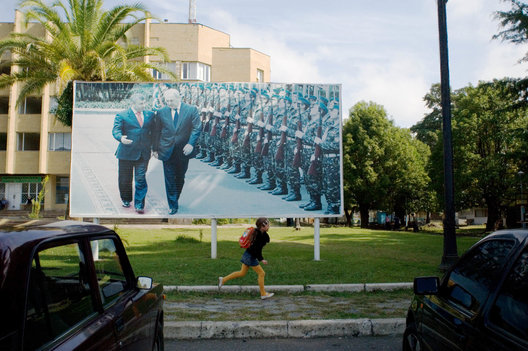 A young girl runs past a photo honoring twice elected president of Abkhazia, Sergei Bagapsh.