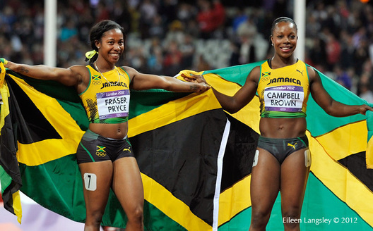 Shelly-Ann Fraser Price and Veronica Campbell-Brown (Jamaica) pose with the national flag after thei success in the 100 metres at the 2012 London Olympic Games.