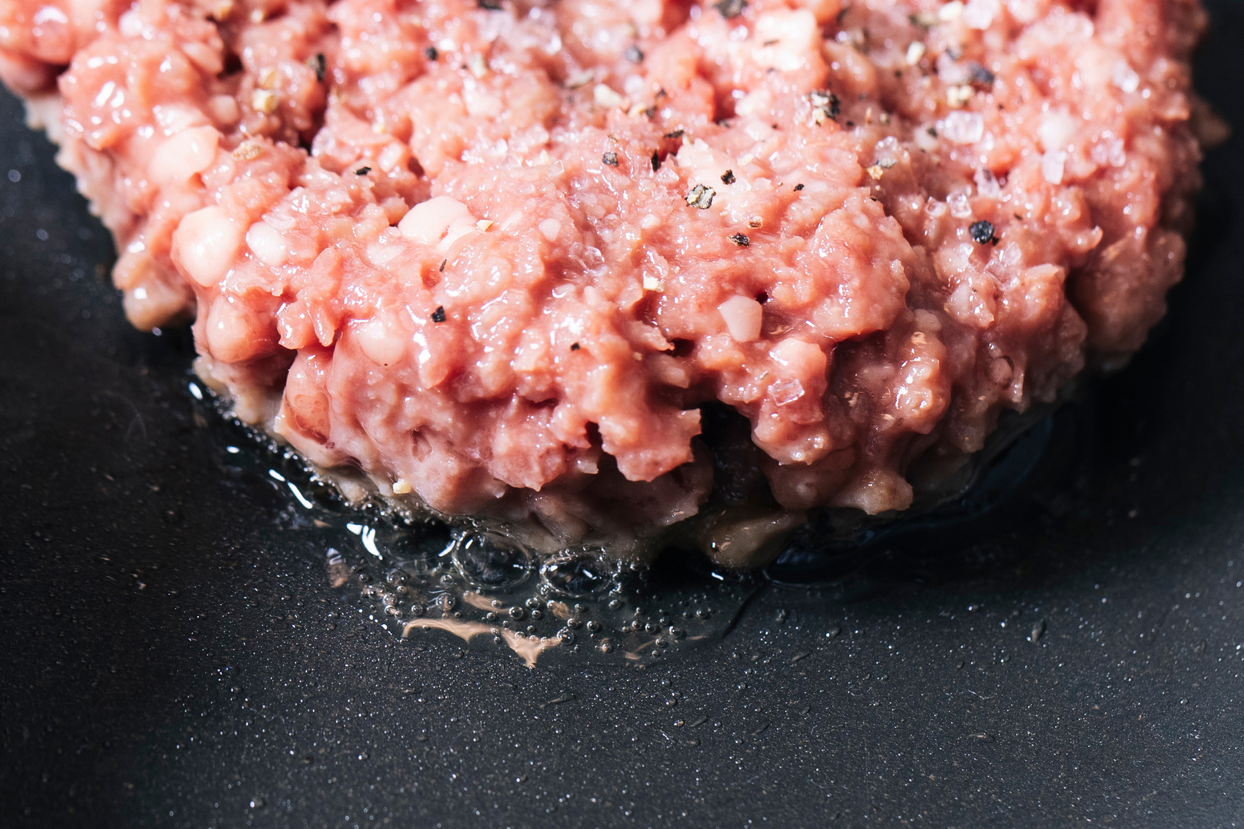 Impossible burger patties are being cooked on a pan at the test kitchen inside Impossible Foods headquarters in Redwood City, Calif. on Thursday, June 20, 2019.