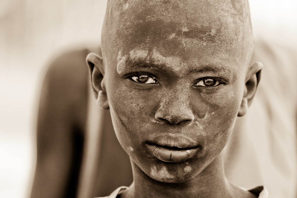 The white marks on the face of a Dinka boy in a cattle camp in South Sudan are the telltale signs of cow dung ash, which is used as a cosmetic and insect repellent.