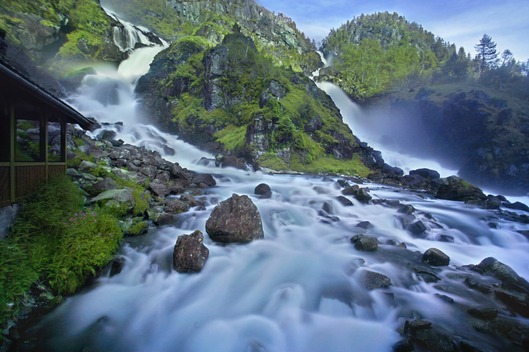 Låtefossen, a famous twin-waterfall in Oddadalen, Hordaland County, Norway. Dropping 541 feet are two separate streams flowing down from the lake Lotevatnet making for a spectacular (and wet) view as one drives over the old, stone, six-arched bridge.