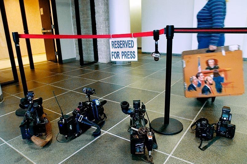 News cameras are lined up as a courtroom sketch artist enters a courtroom in Riverhead, NY.