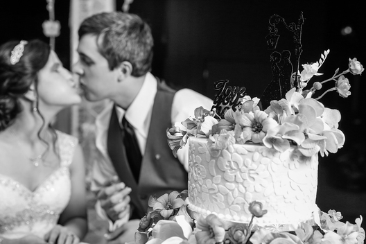 wedding couple kissing behind wedding cake