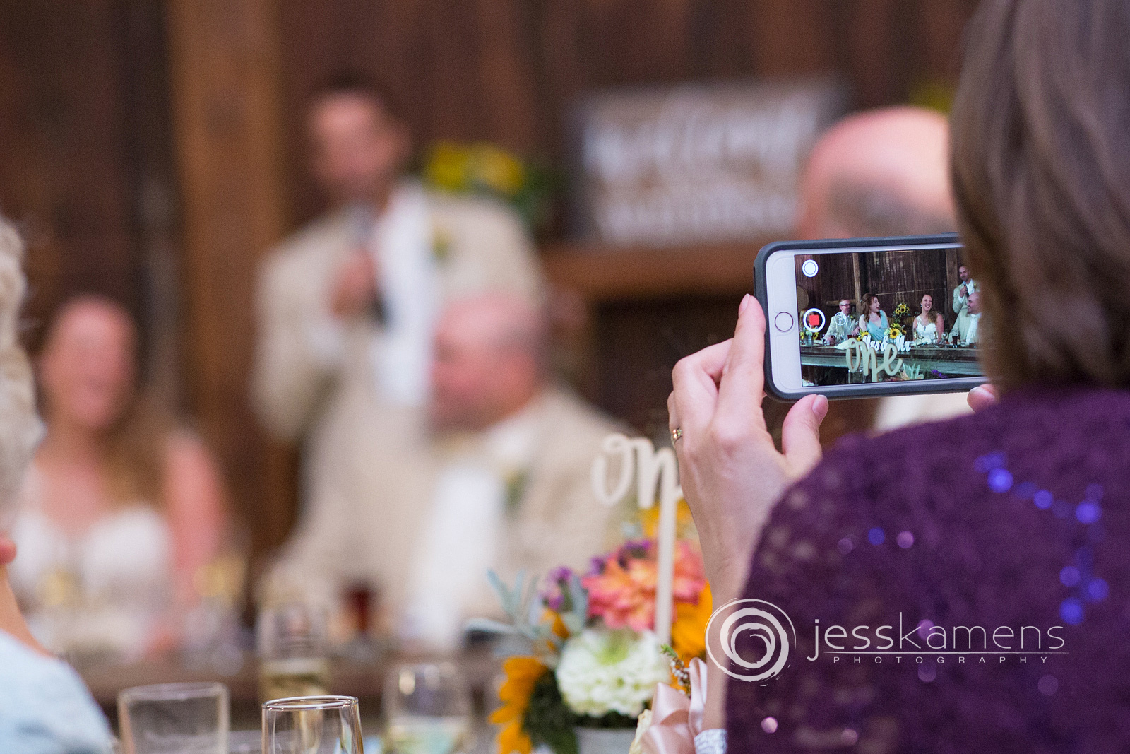a guest takes a picture on her phone of the bride and groom