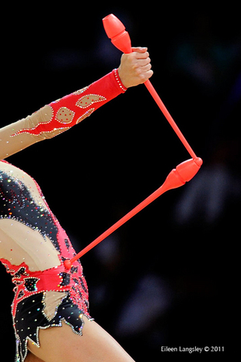 A generic image of a gymnast posed with Clubs at the start of her routine.