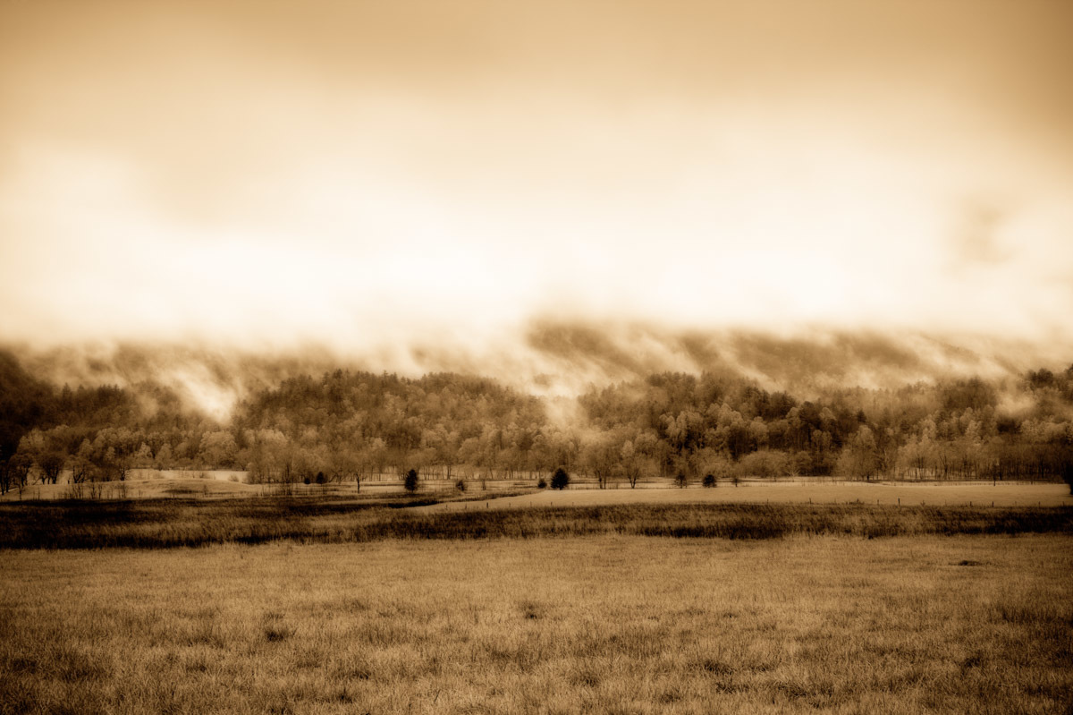 "The Smoky Mountains are named after the mist that appears at the end of the rainstorms (as seen from Cades Cove, next to the Smoky Mountains National Park in Tennessee). This image, sepia-tinged, is from my ""Landscapes and Dreams"" Collection.   I pressed the shutter button on my digital SLR camera to capture these fleeting moments at various times, but it was only in the last few months of 2008 that I began to explore a new process of developing these digital photographs. The resulting images form my Landscapes & Dreams collection, made by combining two copies of each single photograph, each copy altered from the original in a certain way. The juxtaposition of these two revised copies results in the final effect."