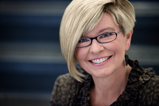Business headshot of smiling blonde woman with glasses by commercial photographer Nancy Rothstein