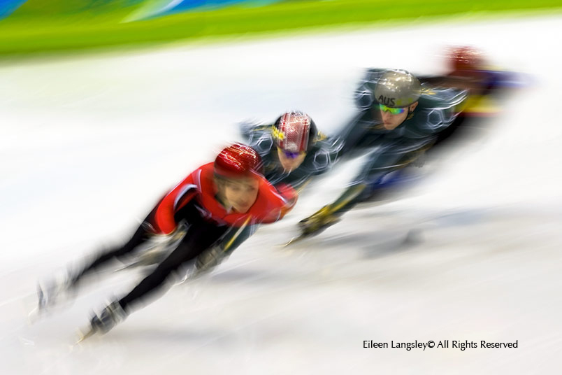 A blurred motion image of short track speed skaters in training at the 2010 Winter Olympic Games in Vancouver.