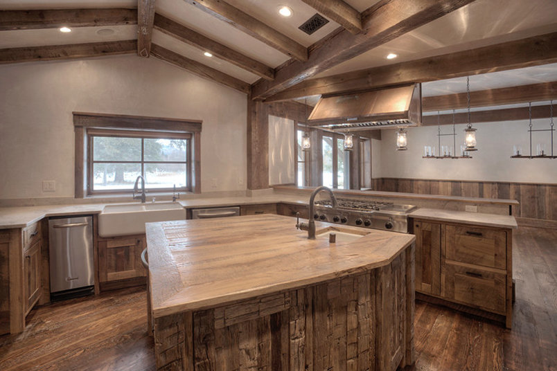 Honed limestone counters, a patinaed copper hood, lantern bar lights and a reclaimed oak counter on the island create a sensory experience of rustic materials. The original structural window resides above the kitchen apron sink.