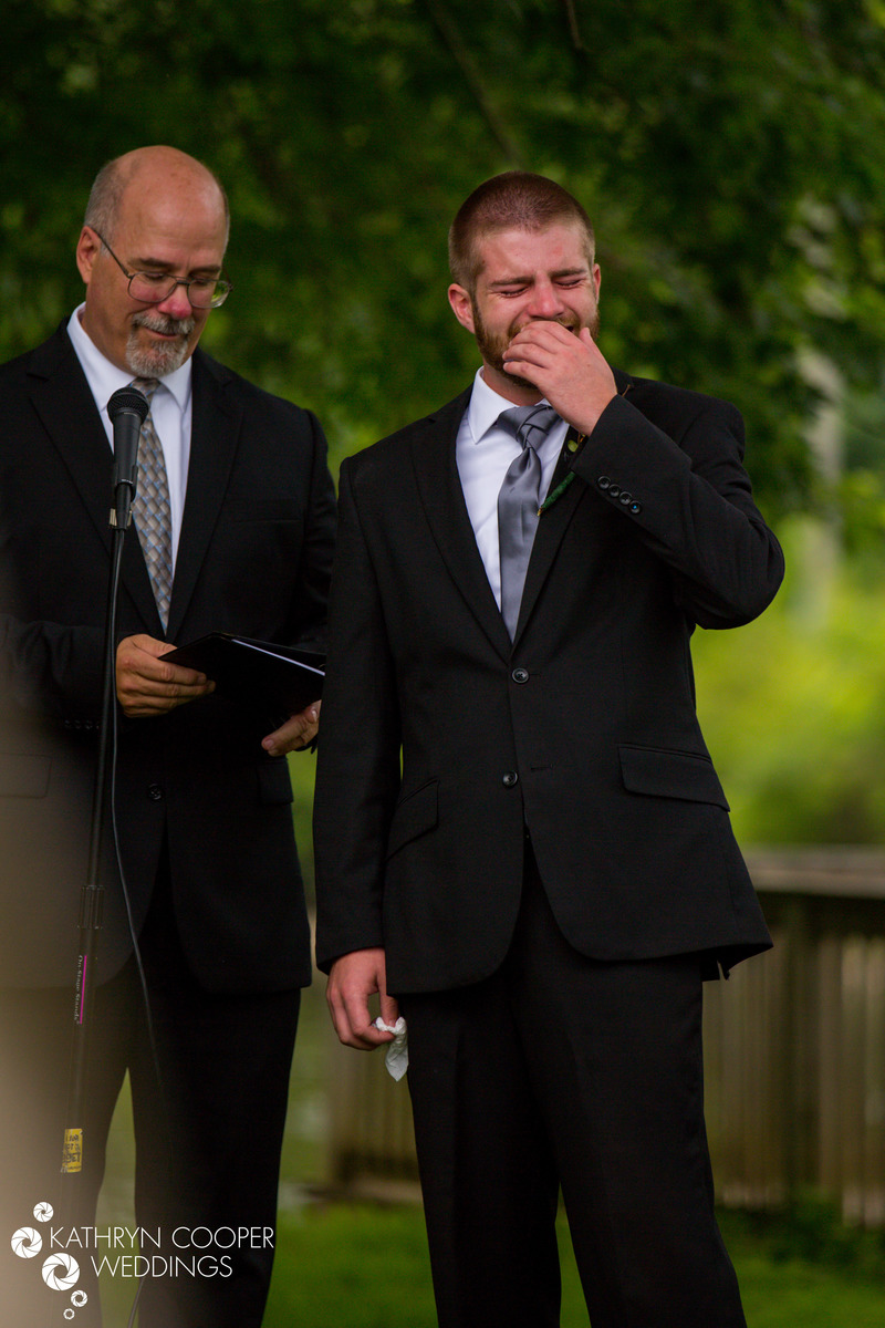 Emotional groom crying as he sees his bride come down the aisle for the first time at Christian wedding