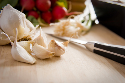 Cloves of garlic, green onions, and radishes on a cutting board with paring knife - Chad Jackson | Jackson Visuals