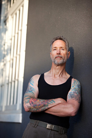 Editorial portrait of tattooed male in black tank top leaning against wall by commercial photographer Nancy Rothstein