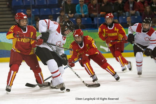Switzerland's Kathrin Lehmann comes under pressure during their Women's Ice Hockey match against China.
