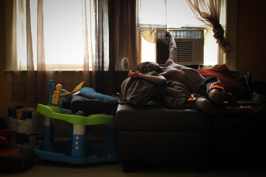 Her son relaxes in front of A/C on a hot summer afternoon.