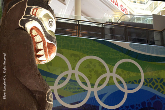 A First Nations Totem Pole looks across to the Olympic Rings displayed in the lobby of the Main Press Centre at the 2010 Winter Olympic Games in vancouver