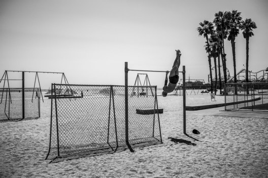 Strange Days; Life Under Covid 19. Despite the public health order closing the beaches and The Original Muscle Beach under look and key, a determined fitness enthusiast manages to find a way to get in a workout.