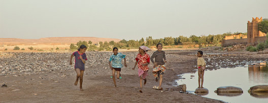 Children races each other on a dried river bottom.