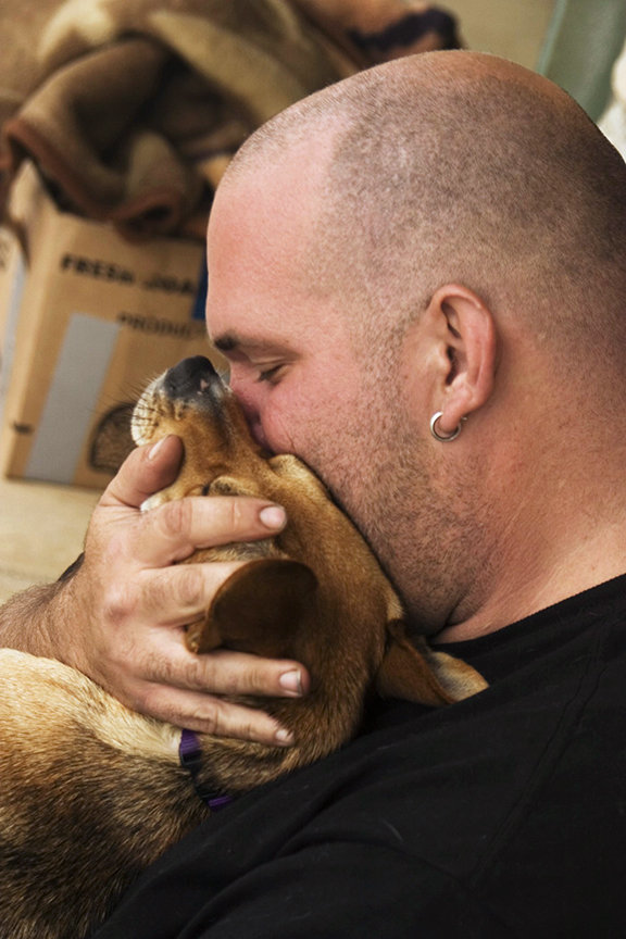 "Joshua, at six-foot-four-inches tall and 380 pounds, is, as he said, ""a big guy."" But he becomes a ""big softie"" with his pooch Sparky. He snuggles and kisses his small lap dog as they sit and wait for food donations on the sidewalk at the HB Pier."