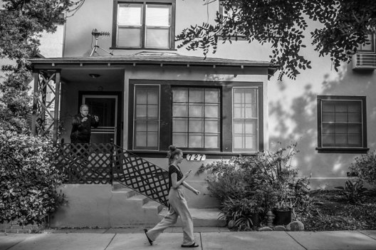 Strange Days; Life Under Covid-19. Joe Lopez of Santa Monica, practices his daily Qigong ritual on his doorstep, as a timely passer-by almost seems to exemplify the collective yearning for human contact.