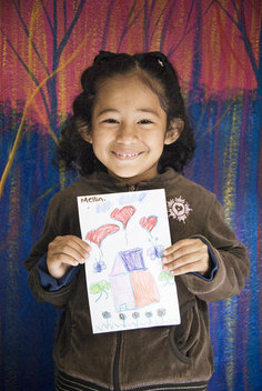 Mellin proudly holds up a drawing she drew for the children in Northfield, Minnesota.