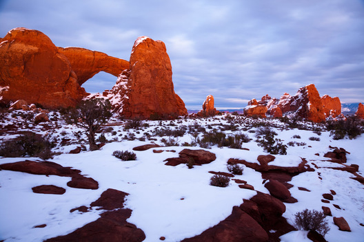 The South Window in Arches National Park, near Moab, Utah, glows a deep orange at dusk.