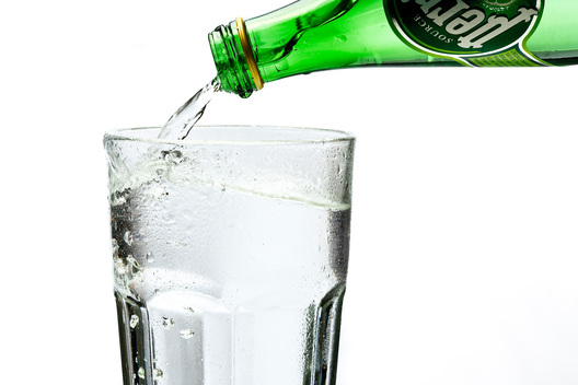 A green bottle of refreshing sparkling Perrier being poured into a chilled glass for enjoyment.