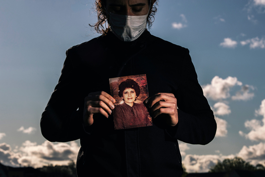 Amir, last name withheld, holds a photograph of his late mother, 68-year old Azar Ahrabi, who was Bay Area's first COVID-19 victim and the first case of community infection in Santa Clara County, stands for a portrait in Santa Clara, Calif. on Wednesday, March 25, 2020.