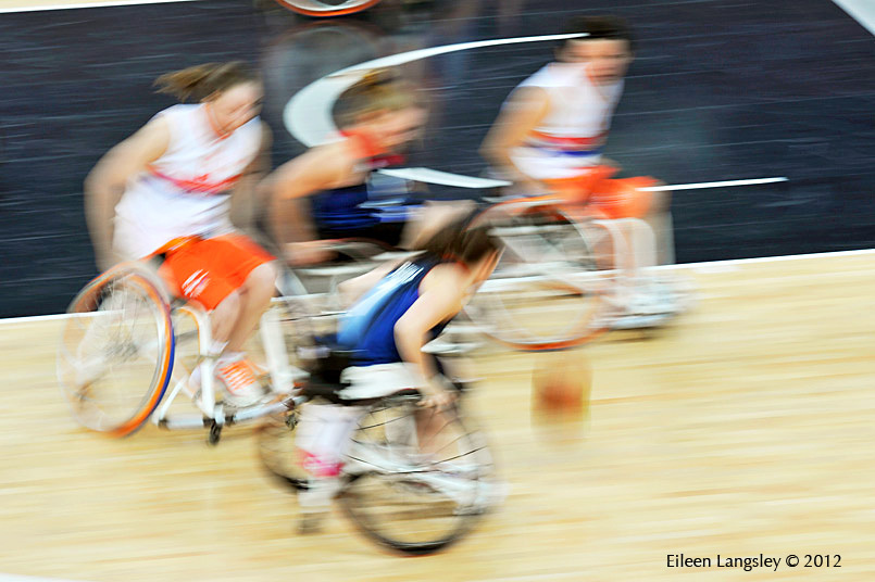 A geberic blurred motion image of players rushing to get to the ball first in the Great Briatin V Netherlands Women's Wheelchair Basketball match at the London 2012 Paralympic Games.