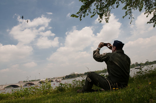 A military spectator photographs vintage planes from the bank of the Potomac River.