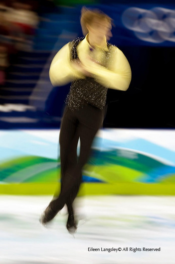 A generic blurred motion image of a male skater performing a jump during his free programme at the 2010 Winter Olympic Games in vancouver.