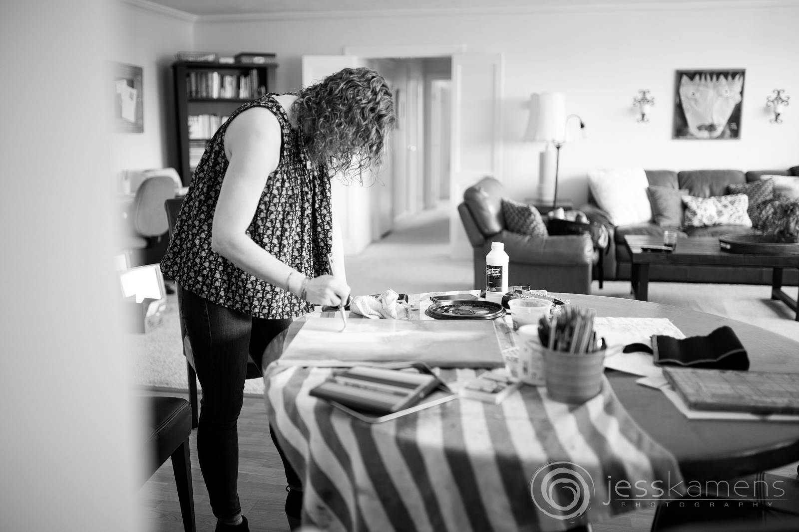 A black and white image of Renée painting in her home