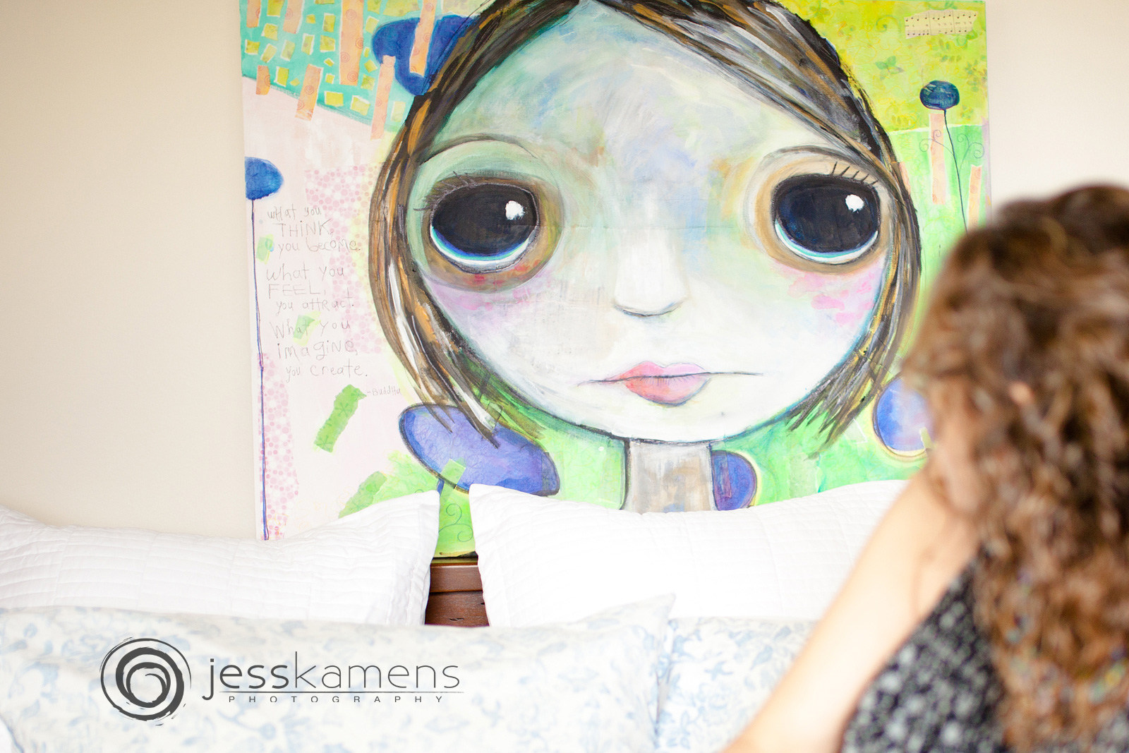 Renée looking at a large portrait of a girl with large eyes in her bedroom