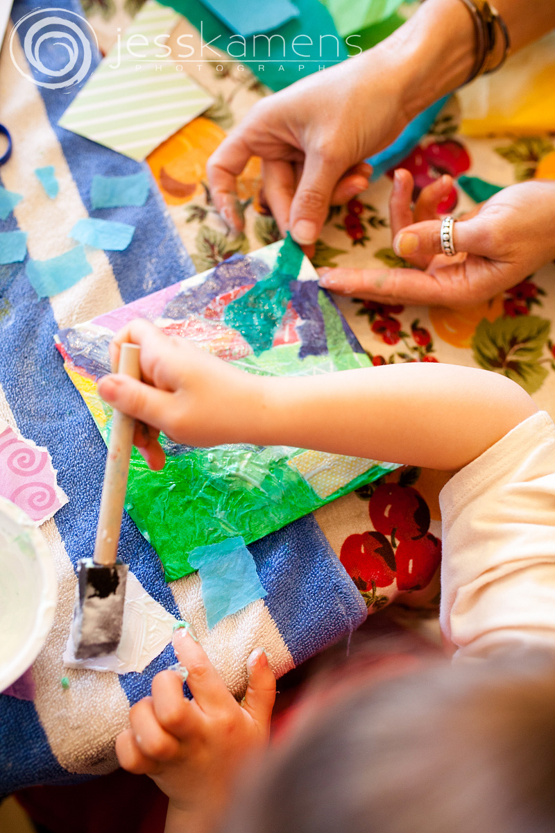 a woman's hands and a child's hands making art