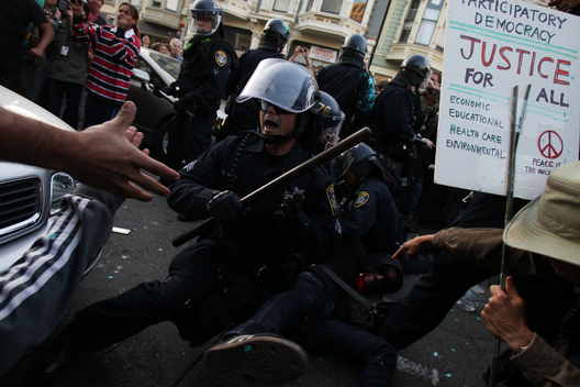 "A police officer attempts to control the scene after being surrounded while making an arrest at an ""Occupy Wall Street"" demonstration in response to an early morning police raid which displaced Occupy Oakland's tent city in Oakland, California October 25, 2011."