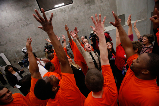 San Francisco Sheriff's Captain Kevin Paulson (C) and Eliana Lopez, wife of San Francisco Sheriff Ross Mirkarimi (R), cheer with a group of inmates after dancing together in opposition of violence against women in a One Billion Rising event at the San Francisco County Jail #5 on Valentine's Day in San Bruno, California February 14, 2013. The event, with participants from 250 countries performing a choreographed dance routine on a day associated with romantic love, aims to raise awareness about violence against women in which one in three women across the globe will be raped or beaten in their lifetime.