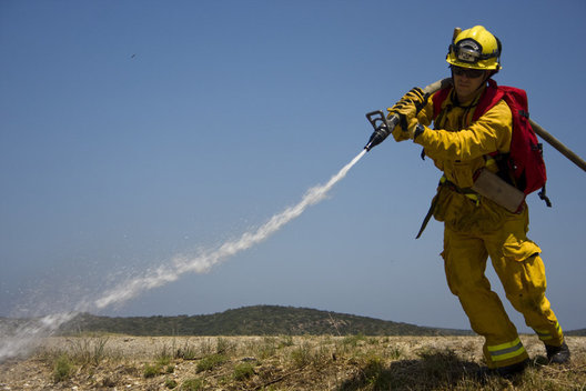 Newport Beach firefighter Justin Dean soaks the ground during a wildland fire training exercise on Tuesday. The hose used for wildfires is lighter, longer and can be extended.