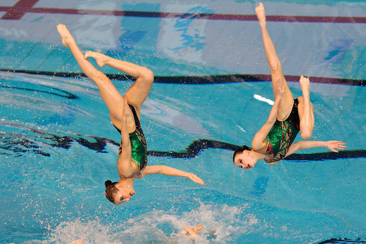 The Russian team show the results of their hard work in training with a perfect double somersault during their routine.