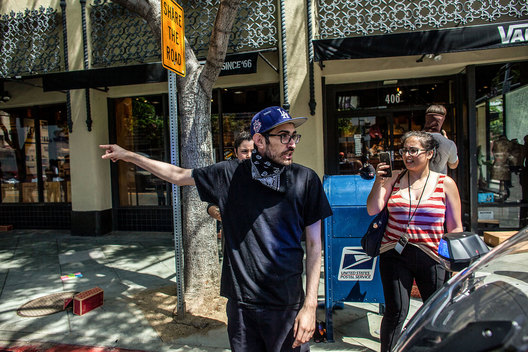 As mass looting takes place in Santa Monica, California, Sunday, May 31, 2020, a bystander directs Police to apparent gunshots fired from inside a jewelry store. The death of George Floyd, an African-American man in police custody, has ignited protests across the country.