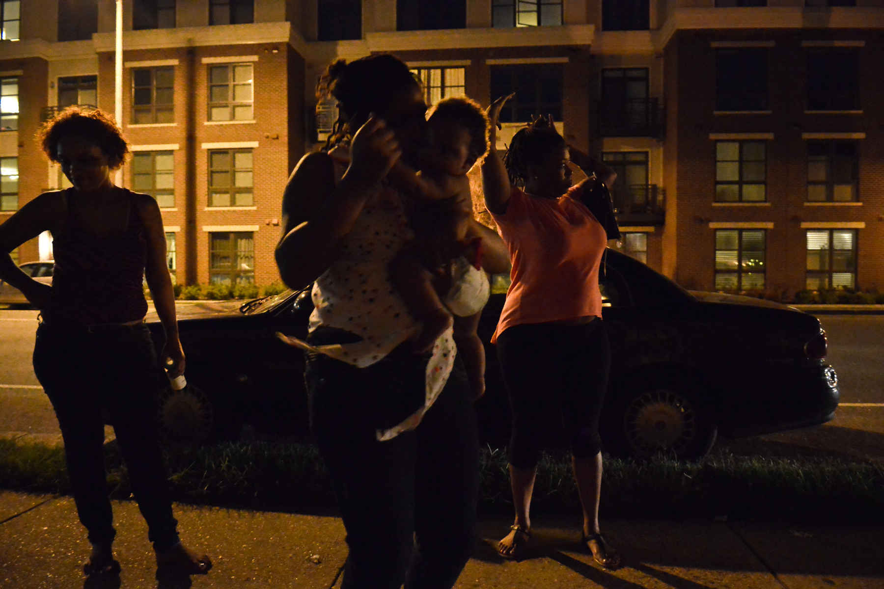 Hanging out on the street at night with a friend.  Her 10 year-old daughter dances with the baby.