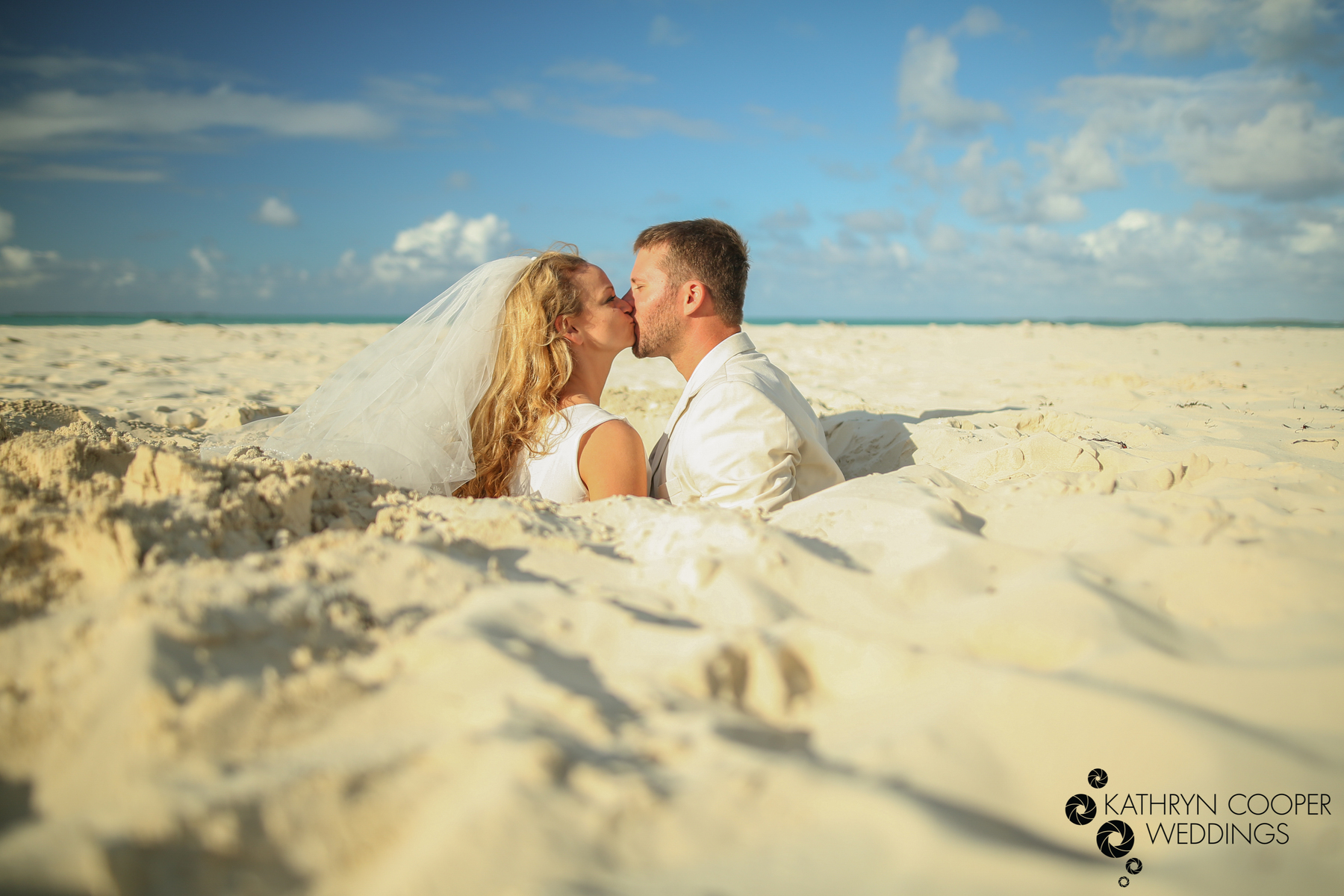 Destination beach wedding Bahamas with couple in sand kissing