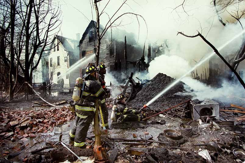 CITY 4/15/01 VOLPE:  Firefighters battle a four alarm fire on Ferry St that devestated three houses Monday morning.