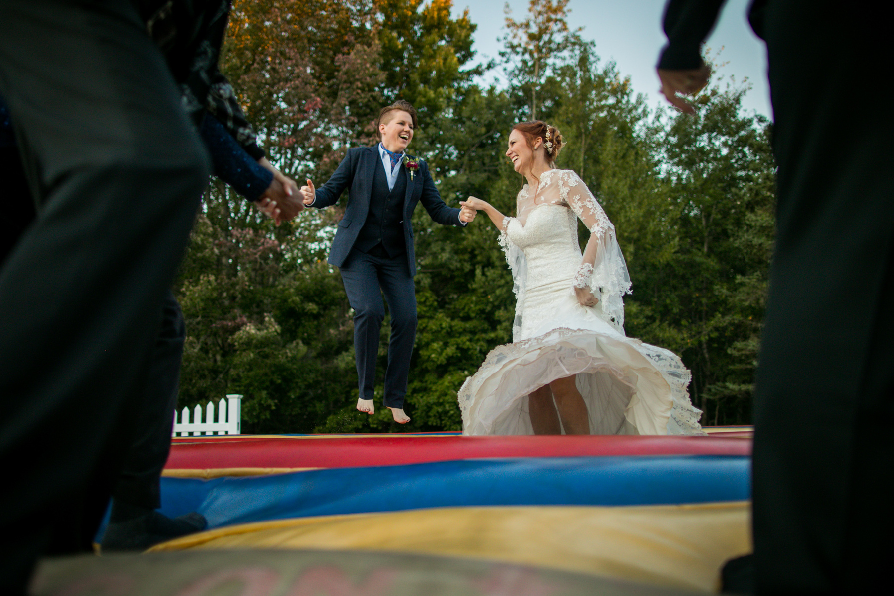 Unique wedding photographer in Acadia National Park, Maine with fun lesbian couple jumping in bouncy house for KOA camping wedding