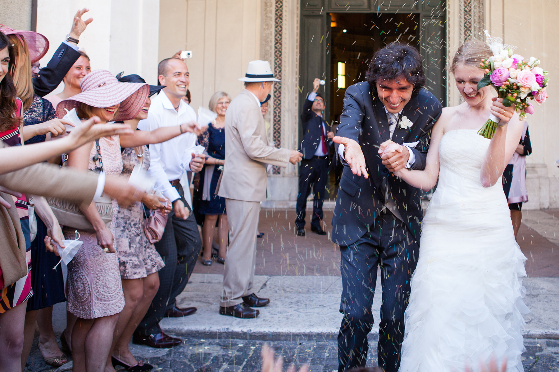 denation wedding in Europe, Rome, Italy specifically where the bride and groom are exiting the church and rise is thrown on them
