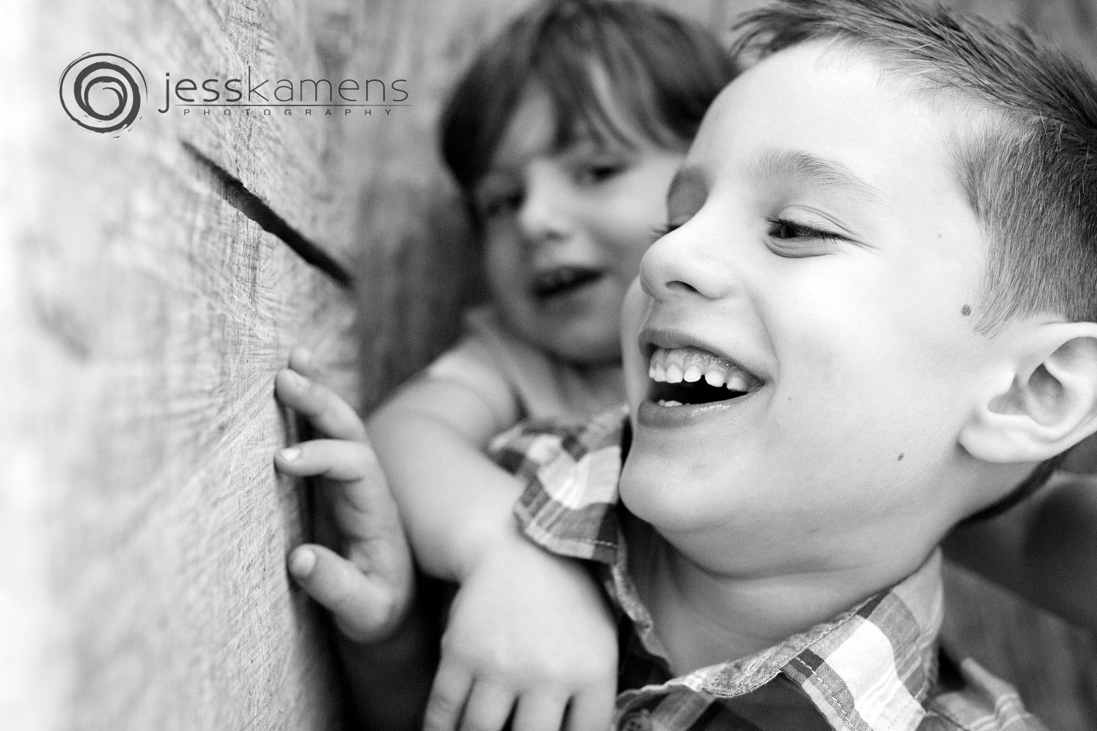 a boy and his brother play in a wooden house during their lifestyle family session