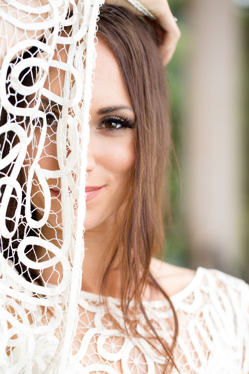 a beautiful bride holds her lace gown over half of her face at the waterfront lodge abraham lincoln park