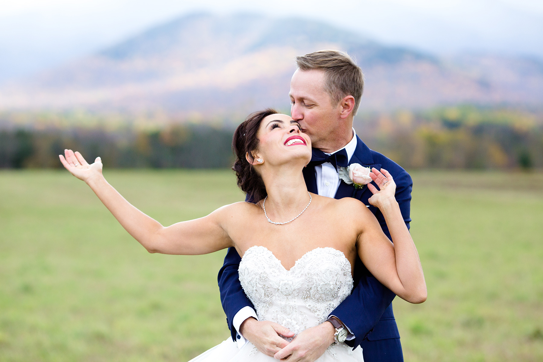 This beautiful destination wedding was in lake placid new york and you can see the mountains in the background. The groom is hugging the bride and this was taken by a