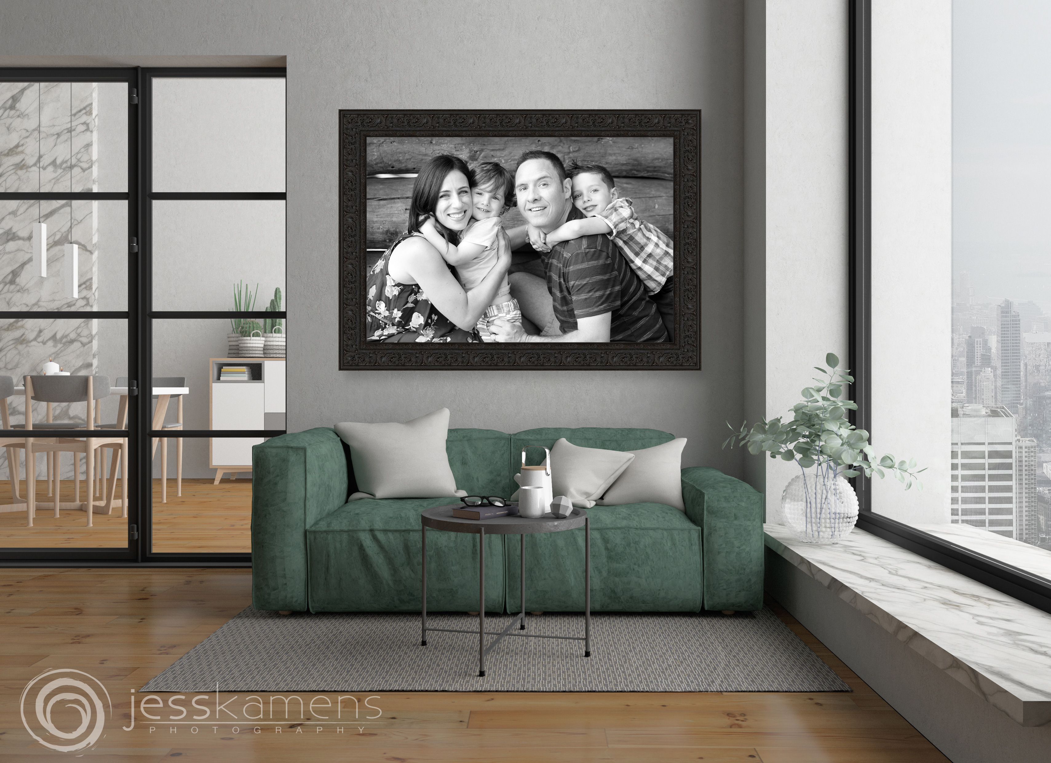 a beautfiul large framed canvas hangs above a green sofa in a living room. The portrait is black and white and of a family with a mom, dad and two boys hugging each other.
