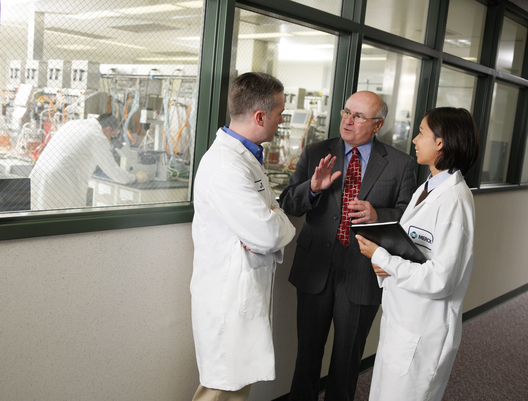 Mr. Richard T. Clark conversing with Merck researchers James Warren, Senior Research and Biomedical Engineer, and Samantha Ozuna, Research Biochemical Engineer.