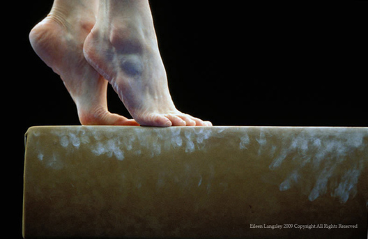 A generic image of the feet of a gymnast poised on the end of the Balance Beam during her competitive routine.